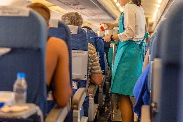 Les agents de bord servent des boissons aux passagers à bord. Photo Premium