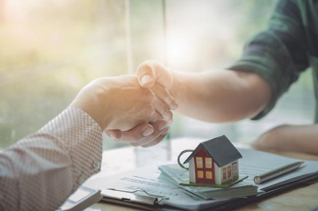 Les agents immobiliers acceptent d'acheter une maison et de remettre les clés aux clients dans les bureaux de leur agence. Photo Premium