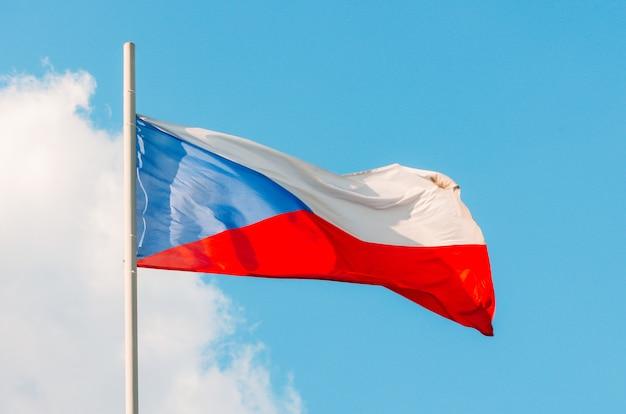 Agitant Le Drapeau Coloré De La République Tchèque Sur Le Ciel Bleu. Photo Premium