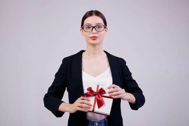 Agréable Femme D'affaires Jolie Est Debout Sur Gris Avec Un Cadeau Dans Ses Mains Dans Une Veste Noire Et Un T-shirt Blanc. Minute De Bonheur. Pas Besoin De Travailler. Photo Premium