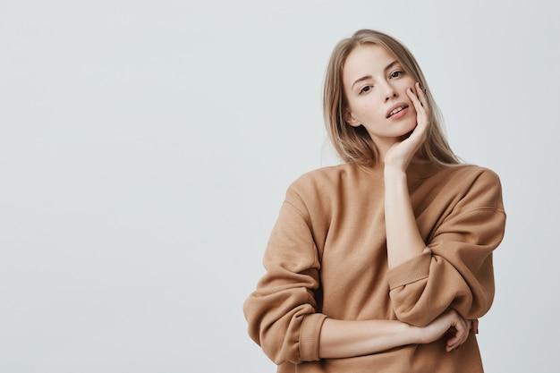 Agréable Femme Blonde Séduisante Vêtue D'un Pull Ample Beige Avec Des Yeux Sombres Attrayants Et Des Lèvres Entrouvertes Photo gratuit