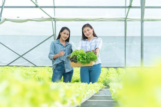 Agriculteur Asiatique Heureuse Tenant Un Panier De Légumes Et Une Tablette Et Souriant Photo Premium