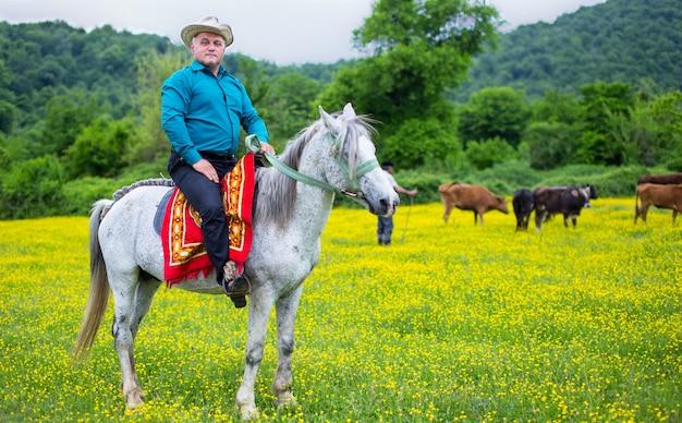 Agriculteur à cheval soignant des vaches dans la plantation Photo gratuit