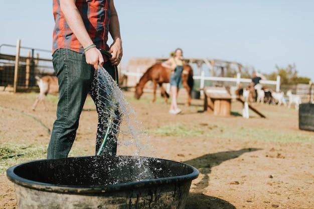 Agriculteur Remplissant Une Baignoire Avec De L'eau Photo gratuit