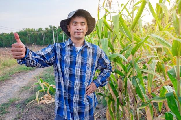 Agriculteurs asiatiques mâle debout pouce dans la ferme de maïs à la thaïlande Photo Premium