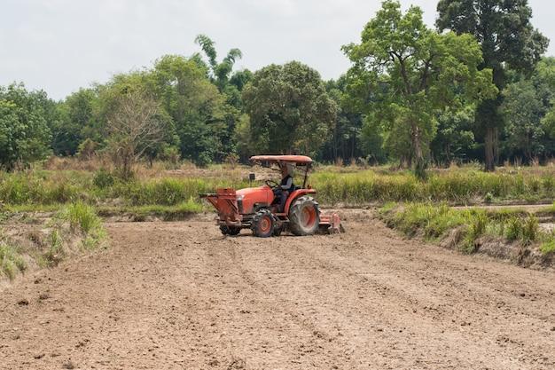 Les agriculteurs thaïlandais utilisent un tracteur pour préparer le sol à la culture du riz. Photo Premium