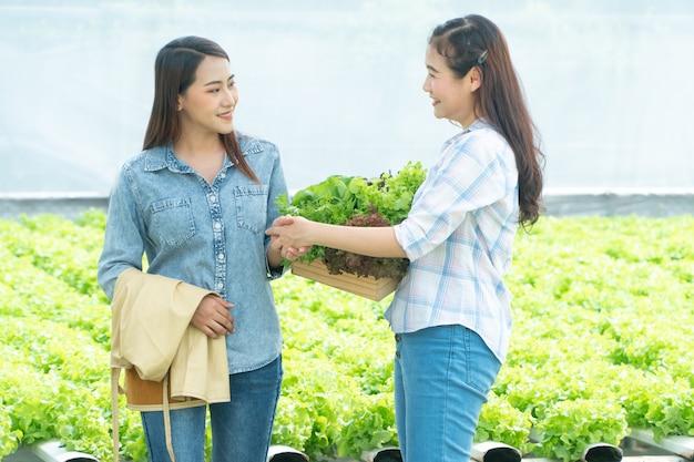 Agricultrice Asiatique Tenant Un Panier De Légumes Et Serrer La Main De Partenaires Après La Réussite De L'accord. Photo Premium