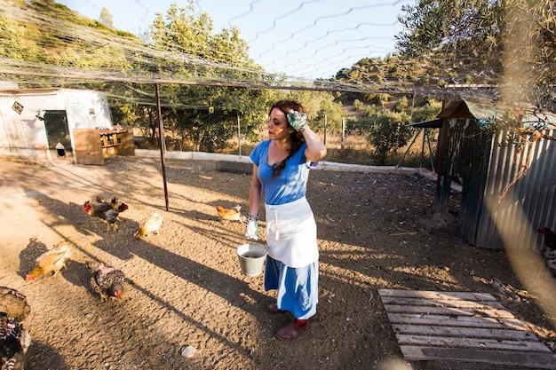 Agricultrice épuisée nourrissant le poulet dans le champ Photo gratuit