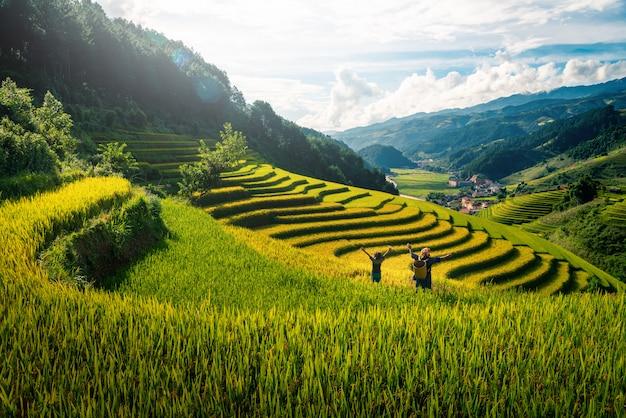 Agricultrice et fille levant le bras sur les champs de riz en terrasse au coucher du soleil au vietnam. Photo Premium