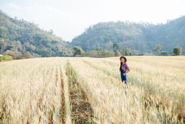 Agricultrice Avec La Saison De Récolte Du Champ D'orge Photo gratuit