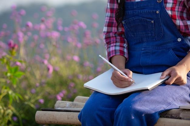 Les agricultrices prennent des notes dans le jardin de fleurs. Photo gratuit