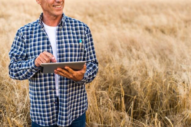 Agronome de la vue moyenne avec une tablette Photo gratuit