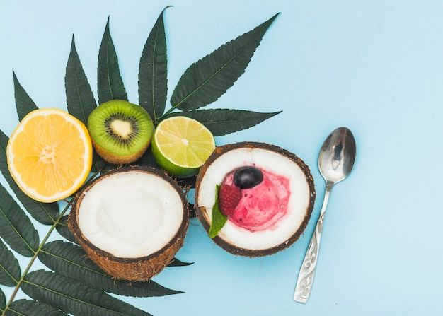 Les agrumes; kiwi; noix de coco coupées en deux avec une cuillère à crème glacée et une cuillère sur fond bleu Photo gratuit