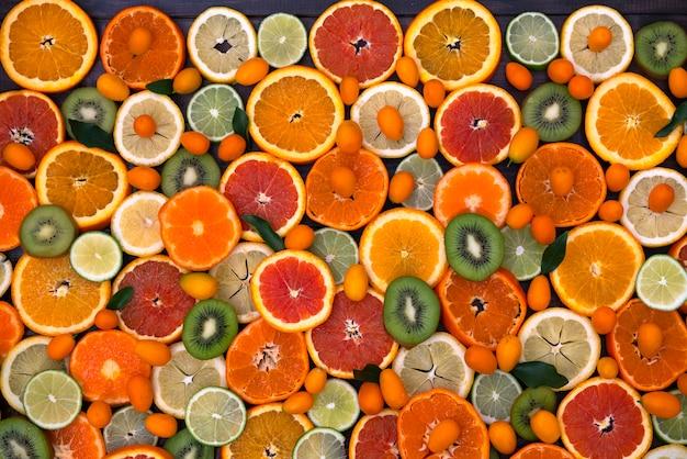 Des agrumes, des mandarines, des kiwis, des citrons et du citron vert mélangés se trouvent sur un bois noir Photo Premium