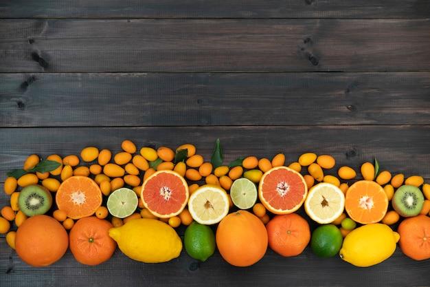 Des agrumes, des mandarines, des kiwis, des citrons et du citron vert mélangés se trouvent sur un fond en bois noir de planches. Photo Premium