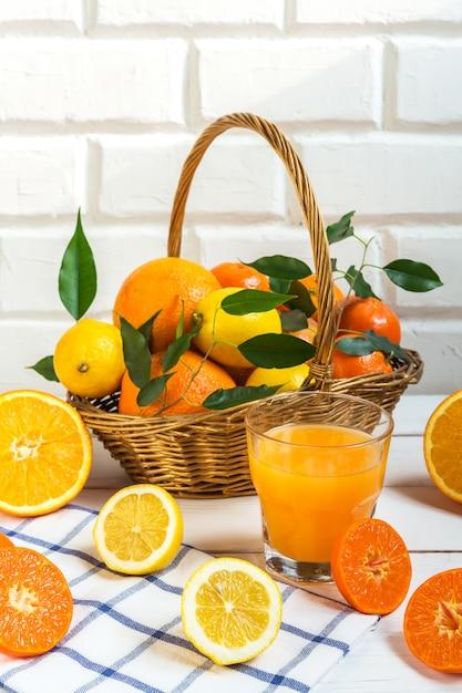 Agrumes orange citron dans un panier et jus sur un fond clair, régime alimentaire sain Photo Premium