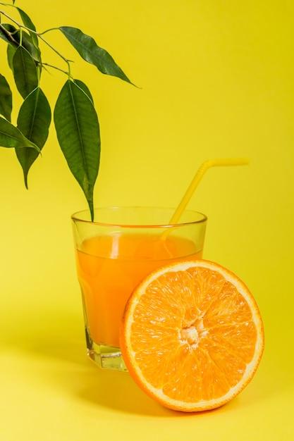 Agrumes orange citron dans un panier et jus sur fond jaune, régime alimentaire sain Photo Premium