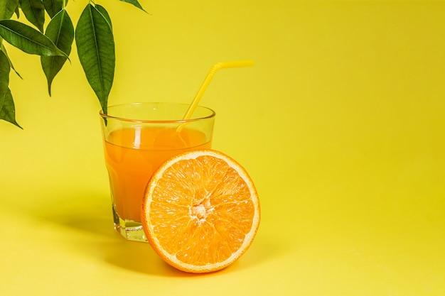 Agrumes orange citron dans un panier et jus sur fond jaune Photo Premium