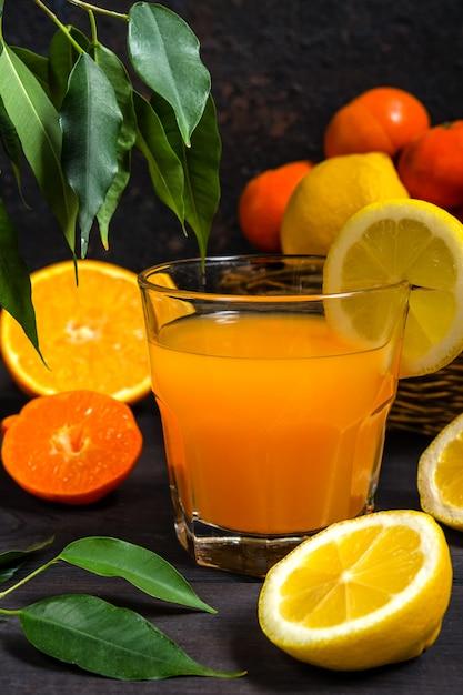 Agrumes orange citron dans un panier et jus sur un fond sombre Photo Premium