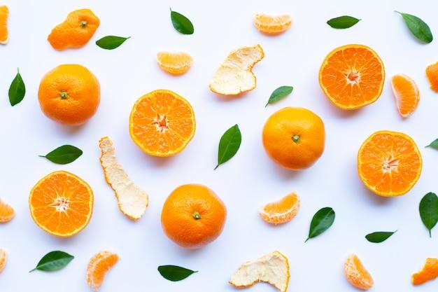 Agrumes orange frais avec écorce et feuilles vertes sur blanc Photo Premium