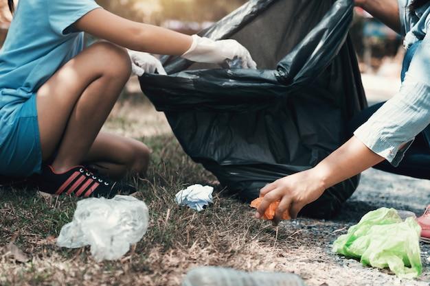 Aide mère et enfant ramasser les ordures au parc Photo Premium