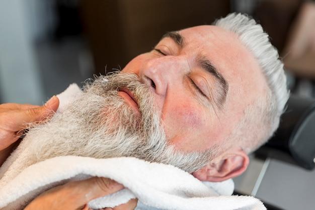 À l'aide d'une serviette sur la barbe d'un homme âgé dans le salon de coiffure Photo gratuit
