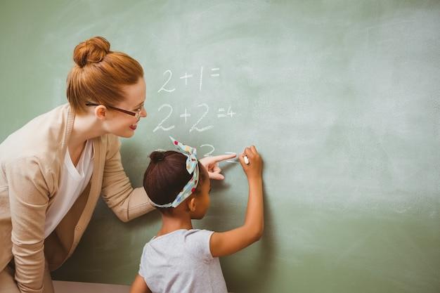 Aider une fille à écrire sur un tableau noir dans la salle de classe Photo Premium