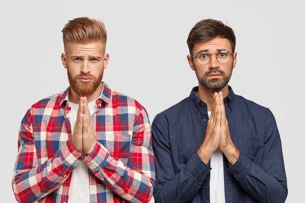 Aidez-nous Une Fois De Plus. Deux Amis Barbus Ont Des Expressions Moyennes, Se Tiennent La Main Pour Prier, Demander Des Excuses Ou Pardon Photo gratuit