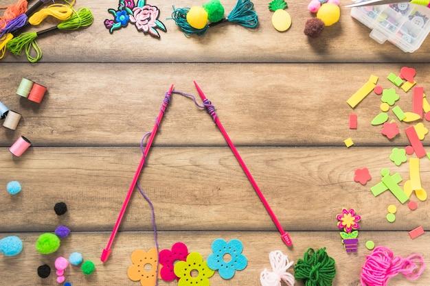 Aiguilles tricotées avec du fil violet à l'intérieur des éléments décoratifs de la table Photo gratuit