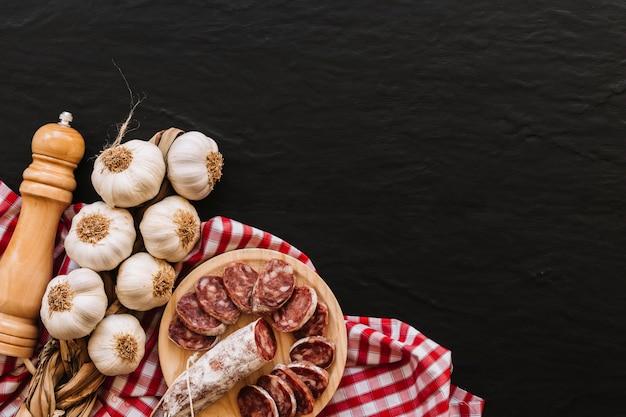 Ail et saucisses près des épices sur une serviette Photo gratuit