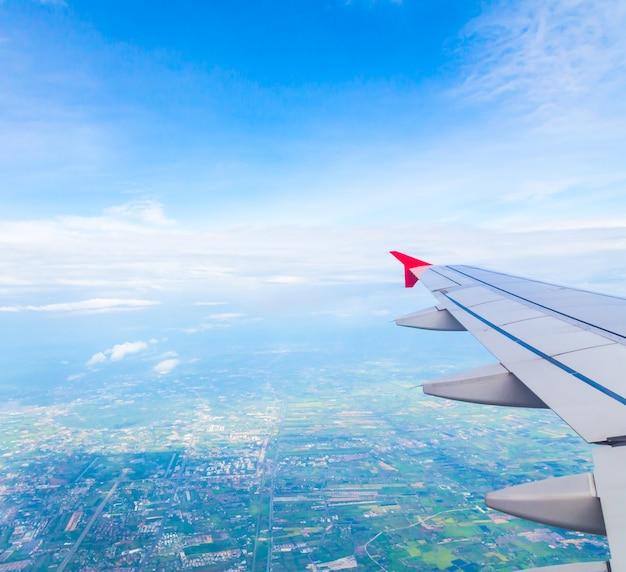 Aile d'un avion avec un arrière-plan de la ville Photo gratuit
