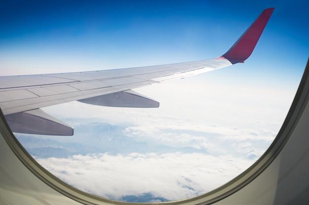 Aile d'un avion volant au-dessus du ciel Photo Premium