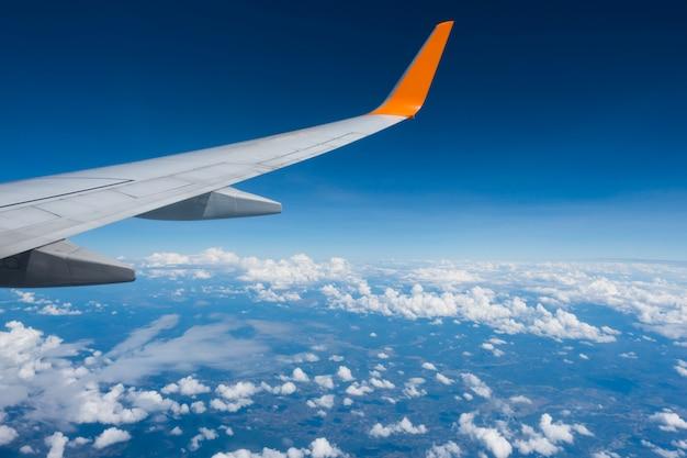 Aile d'un avion volant au-dessus des nuages Photo Premium