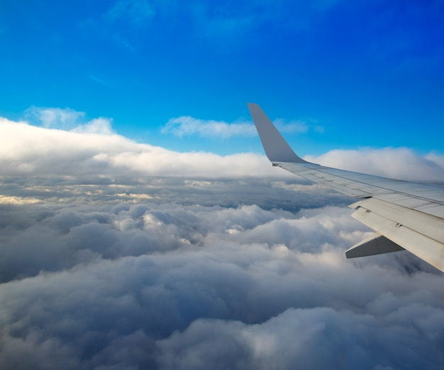 Aile d'avion volant sur une mer de nuages Photo Premium