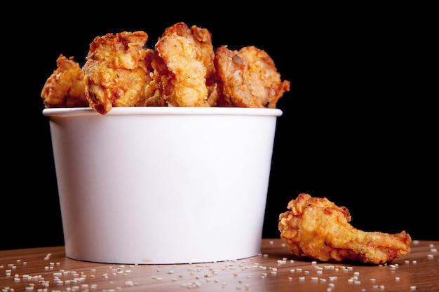 Ailes de poulet bbq dans un seau blanc sur une table en bois et un fond noir. Photo Premium
