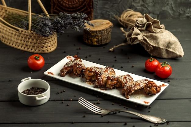 Ailes de poulet cuites dans une sauce teriyaki garnie de sésame Photo gratuit