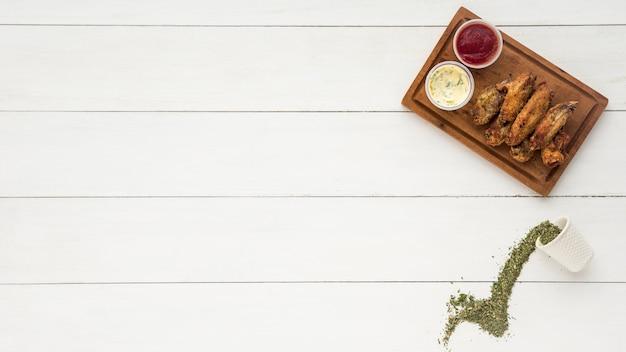 Ailes de poulet épicées avec des sauces et de la verdure Photo gratuit