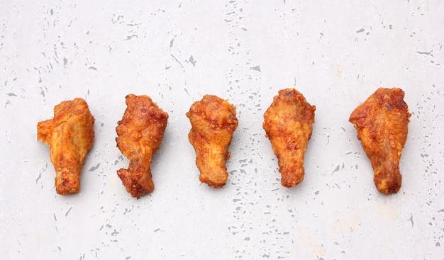Ailes De Poulet Frit Coréen Isolé Sur Fond Gris En Studio. Photo Premium