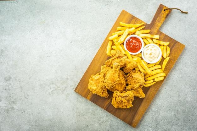 Ailes de poulet frites avec tomates et frites Photo gratuit