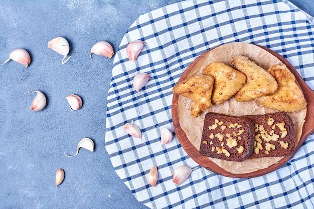 Ailes De Poulet Grillé Aux épices Et Tranches De Pain Sur Une Planche De Bois Sur Bleu Photo gratuit