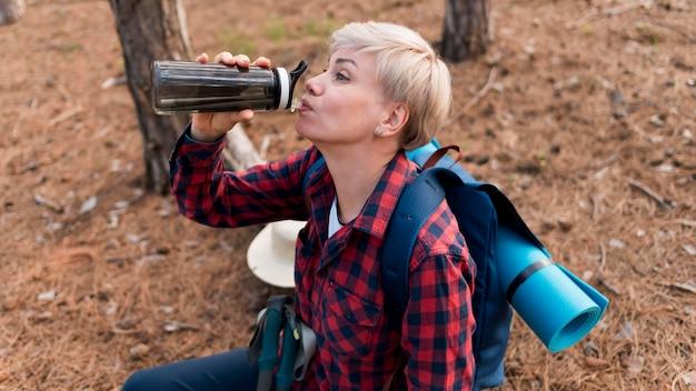 Aîné Femme Touriste Eau Potable Pour L'hydratation Photo gratuit