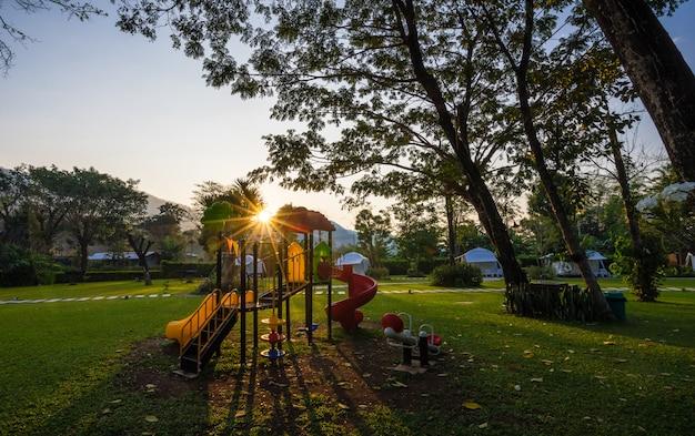 Aire de jeux colorée et lever de soleil sur cour dans le parc Photo Premium