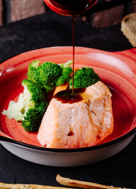 Ajouter La Sauce Teriyaki Au Darne De Saumon Avec Le Brocoli Dans Un Bol Rose. Photo gratuit