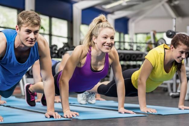 Ajustement des personnes en position de planche dans la salle de sport Photo Premium