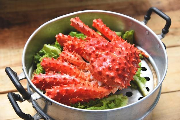 Alaskan king crab aliments cuits à la vapeur sur des fruits de mer en pot et des légumes de laitue sur du bois Photo Premium