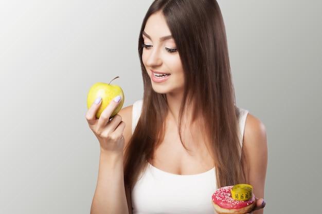 Une Alimentation Saine Et Nocive Une Jeune Fille Choisit Entre Une Alimentation Saine Et Nocive. Photo Premium