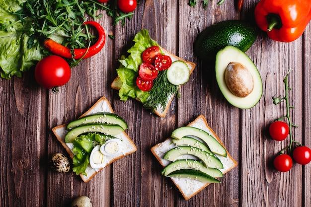 Des aliments frais et sains. idées petit déjeuner ou déjeuner. pain au fromage, avocat et verdure Photo gratuit