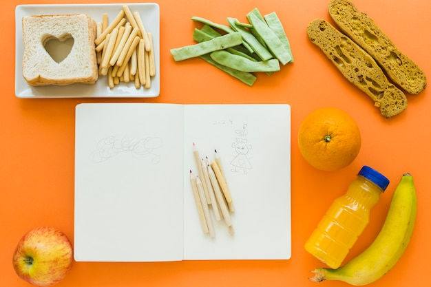 Aliments sains autour de cahier avec des griffonnages Photo gratuit