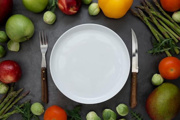 Aliments Sains Ou Concept De Régime. Assiette Ronde Vide Avec Différents Fruits Et Légumes Autour. Mise à Plat. Photo Premium