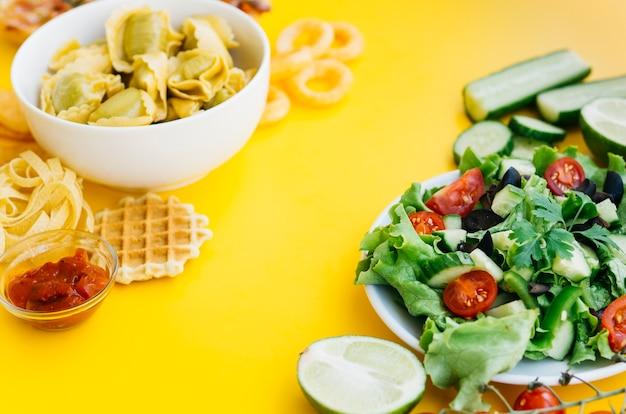 Aliments sains vs aliments malsains sur table jaune Photo gratuit